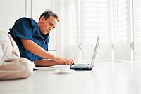 Man using laptop on floor