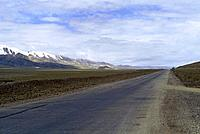 Road through mountains. A long straight road. To vanishing point on horizon. Snowy mountains. Plains. Lhasa to Golmud. 1,127km journey. trip.