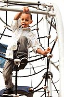 Mixed race boy climbing on structure in playground