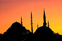 Silhouette of Suleyman Mosque. Spires/ two domes. Minarets. Sunset. Deep orange sky.