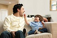 Caucasian father and son eating snack on sofa