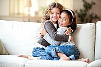 Mixed race girls sitting on sofa hugging