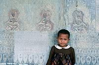 Young boy against stone carvings. Temple buildings.