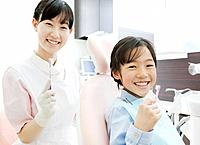A Girl and Dental Assistant Holding Toothbrush