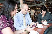 Hispanic business people text messaging on cell phones in cafe
