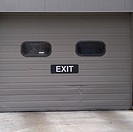 Garage door in a highrise  says Exit The door look like faces