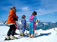 Family in ski gear looking over mountain landscape. Snow.
