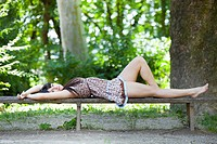 Attractive young woman is lying on a wooden bench in the park