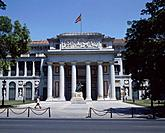 View of Prado Museum. Stone pillars / columns. Statue. Ornate building. Trees. People. Flag.
