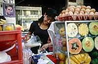 Young woman pouring drink. Fruit juice stall. Cut papaya. Melon. Pineapple. Eggs on tray.