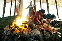 Cree Indian Camp. Medeoewod. Hudson Bay. 28 miles Great Whale. Cree Elizabeth Dick in teepee cooking caribou meat on sticks over fire.