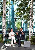 Two Businesspeople Talking on Park Bench