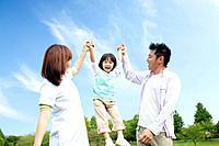 Parents swinging daughter