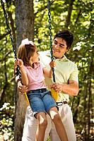 Hispanic father pushing daughter on swing and making eye contact.