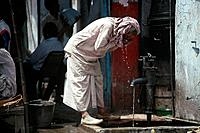 New Delhi. Man drinking from pump in street. Water dripping from hands. White clothes.