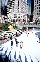Manhattan. Rockefeller Centre. People skating at ice rink. Flags.