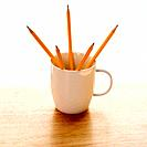 Five pencils in a coffee mug with pointed ends up.