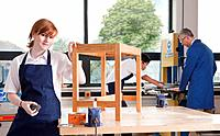 Student in woodworking class putting stain on wooden table