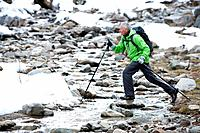 Senior man with backpack and ski poles crossing stream in snowy woods