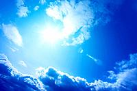 Sun and clouds in blue sky, lens flare