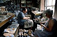 Man and woman in small workshop handmaking leather shoes.