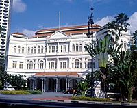Raffles hotel. Refurbished 1990. Facade. Entrance. Traditional colonial style. Fan palm trees.