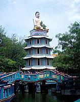 Haw Par Villa. Chinese house and gardens. Pagoda on lake. Seated Buddha statue