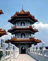 Landscaped park. Pagodas overlooking lake. Three tiers. Decorated roof tiles. Statues on bridge