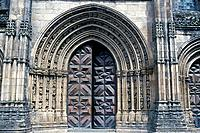 Cathedral. West door. C16th. Gothic arch. Panelled wood door. Stone carvings.