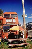 Piccadilly chip shop. Red double_decker bus. Front view. Menu sign. Picnic table with umbrella. Campbell River