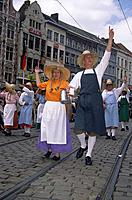Kaiser Karel parade. Man and woman in simple historical dress. Carrying churns/ butter