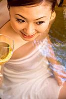 Woman enjoying a glass of wine in a hot tub