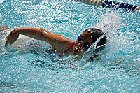 A child competes in a swim meet.