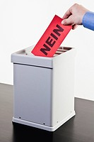 A man putting a ballot with the word NEIN written on it into a ballot box, close_up hands