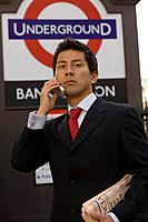 The businessman who applies a cellular phone at the subway entrance in London