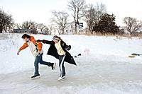 Two teenagers ice skate on a frozen pond near Dunbar, Nebraska.