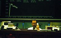 Interior. Frankfurt stock exchange. Man using phone. Seated at computer. Display board,chart.