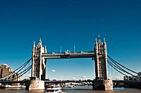 View of London Bridge from the Thames River with tourism boat.