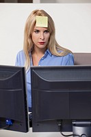 Woman staring at computer with adhesive note on her forehead