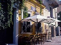 Plaka. Taverna. Yellow painted wall. Tables,chairs. Umbrellas. ArchitectureFood & Drink _ places