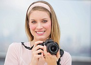 Portrait of young woman holding camera, smiling