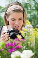 Young woman photographing flowers