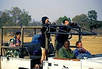 Safari transport. Open topped jeep. People with binoculars,cameras. Driver.