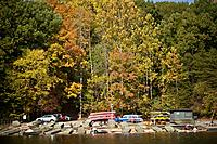 On a fall day, people launch their boats and kayaks on the shore.