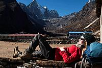 A trekker takes a break in the sun at Merchulu in the Everest region