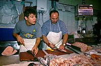 Central covered market. Stall. Fresh fish. Two men filleting fish. Large fish,tuna being cut and prepared.