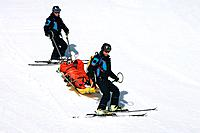 Ski rescue. Ski patrol using a sledge to transport an injured skier from a ski slope.