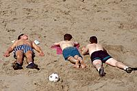 Blackpool Beach. Sand. Three people lying in sun.