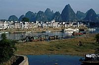 View to town,buildings. Karst limestone rock formations,pinnacles. Houses. Boats on water.