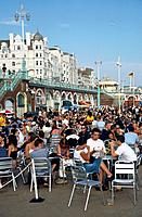 The beach,sea front and Promenade waterfront,in a seaside resort. Tall white buildings on the front,hotels,cafes and people sitting at tables.